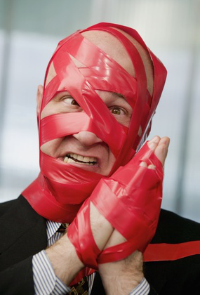 Cross-eyed businessman wrapped in red tape